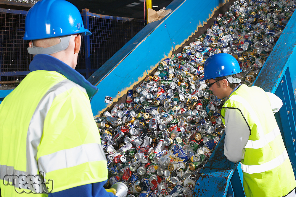 Two workers monitoring conveyor belt of recycled cans back view