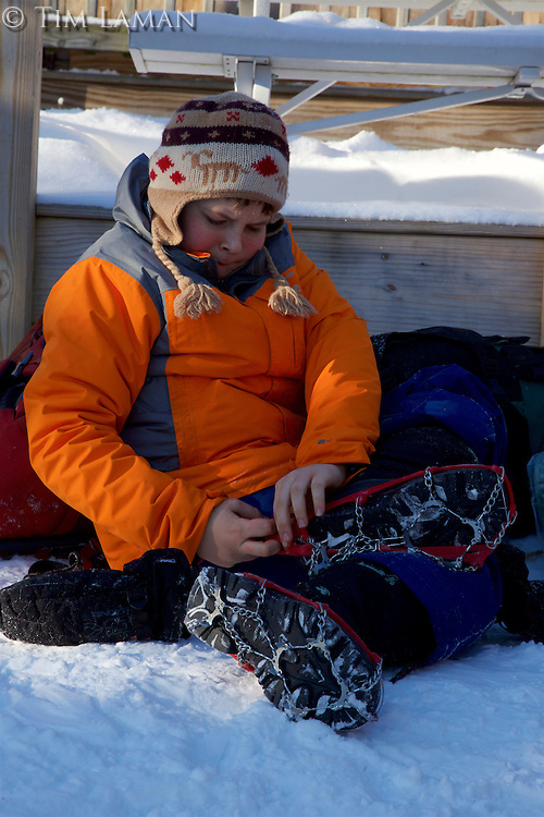 A boy puts on ice cleats/spikes for winter hiking.