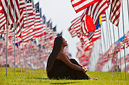Sarah Bender, a Pepperdine University student, sitting among the flag memorial.<br /> Almost 3000 flags memorial marking the tragic events of 9-11, located  at Pepperdine University.<br /> Each flag marks a life lost from 9-11 and their nationality.