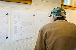 John Carlson studies the architectural blueprints during the open house for the restored fire hall located on the grounds of historic Fort William H. Seward in Haines, Alaska. Carlson, a local expert wood craftsman, will be building the handrail for the staircase to the second floor of the building.<br /> <br /> After being absent from the historic Fort Seward skyline since approximately the 1930s, the 60-foot tower of the fort&rsquo;s fire hall has been restored to its original height. The building and tower, built around 1904 in Haines, Alaska, was shortened to approximately half its height in the 1930s for unknown reasons. The restoration included rebuilding a missing 35-foot section of the 60-foot tower whose purpose was to dry fire hoses. The tower restoration was completed by building its four sections on the ground and then hoisting those sections with a crane into place on top of each other.<br /> <br /> Through the years, the historic Fort Seward area, a former U.S. Army post, has been referred to as Fort William H. Seward, Chilkoot Barracks, and Port Chilkoot. The National Historic Landmarks listing record for the fort says that &quot;Fort Seward was the last of 11 military posts established in Alaska during the territory's gold rushes between 1897 and 1904. Founded for the purpose of preserving law and order among the gold seekers, the fort also provided a U.S. military presence in Alaska during boundary disputes with Canada. The only active military post in Alaska between 1925 and 1940, the fort was closed at the end of World War II.&rdquo; <br /> <br /> The bottom portion of the fire hall is being leased as commercial space. Due to fire code restrictions there is no public access to the upper portion of the tower. <br /> <br /> The fire hall was restored over a two-year period by owners Joanne Waterman and Phyllis Sage who also own the fort&rsquo;s original guardhouse located next door to the fire hall. That building, now known as the Alaska Guardhouse, is a bed and breakfast.