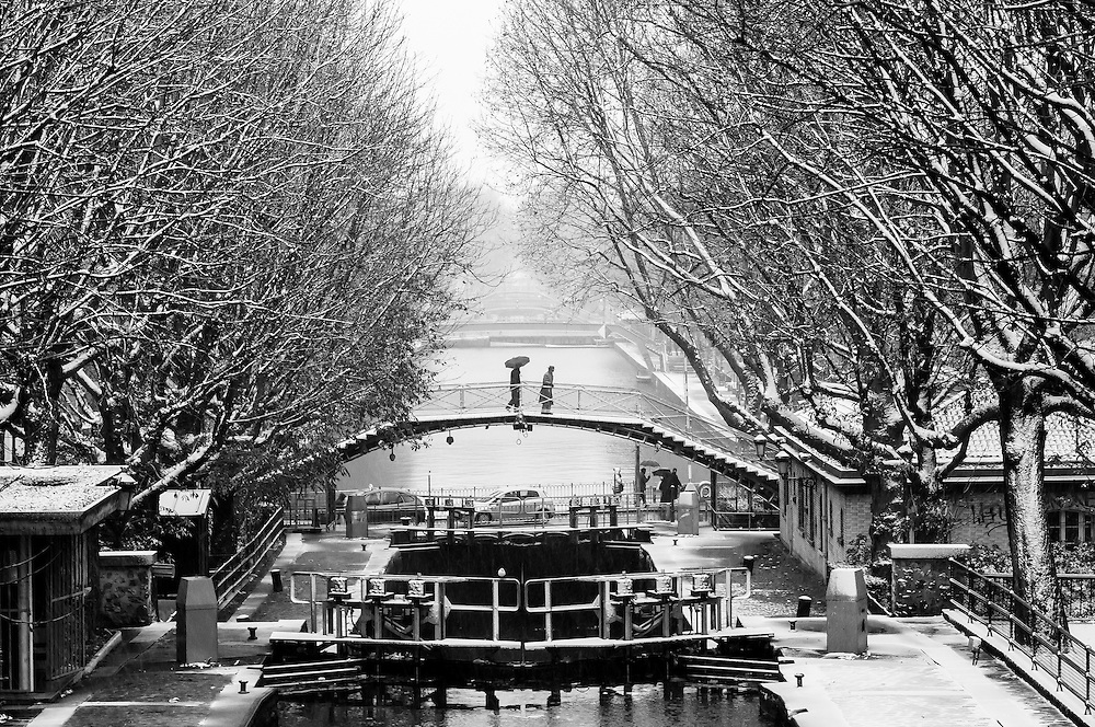 Passersby on a small bridge above the Canal St Martin in Paris.