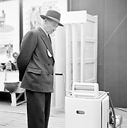 Smartly dressed man looking at a moden washing machine, Finland 1950s