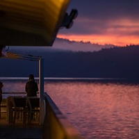 Guests on the National Geographic Venture watch a pastel sunrise reflecting on the water surrounding the San Juan Islands in Washington State.