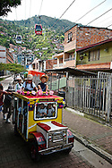 Slum children from the Hillside community of Santo Domingo play on a typical ¨chiva¨or bus, specially made for them, with with The Medellin Metrocable, an aerial tramway, a Metrocable line to service the Comuna, on the background