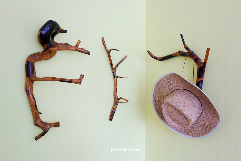 Straw or Panama hat hang on wooden rack. Hand-made artwork. Carving.
