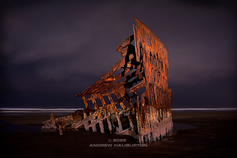 Low tide respite from the pounding surf of the Pacific Ocean, the carcass of the Peter Iredale gets a rinse from a winter rain squall at midnight.  Once a two-thousand ton four-masted steel barque, this bow section is all that remains of the sailing vessel that ran aground on 25 October 1906.  Nikon D700, 28/2 Ai.