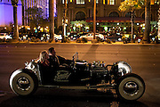 A couple is sitting inside a vintage car travelling along The Strip, Las Vegas, Nevada, USA.