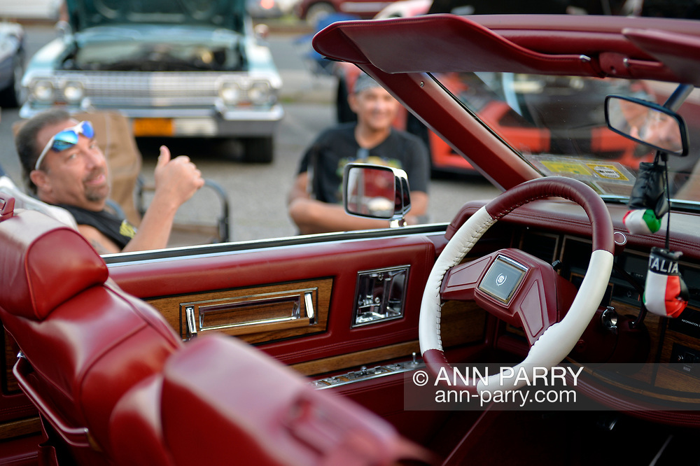 Bellmore, New York, USA. August 24, 2018. Owner Frankie D'Amore, of Levittown sits next to his 1984 white Cadillac El Dorado Biarritz convertible with a particularly fitting license plate number BAC2D80S, at Bellmore Friday Night Car Show.