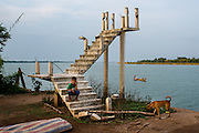 A boys sits on a staircase on the edge of the Mekong near the island of Peam Reang, Cambodia. The stairs are the only remains of a house whose owners were forced to relocate as river erosion wshed away their land.