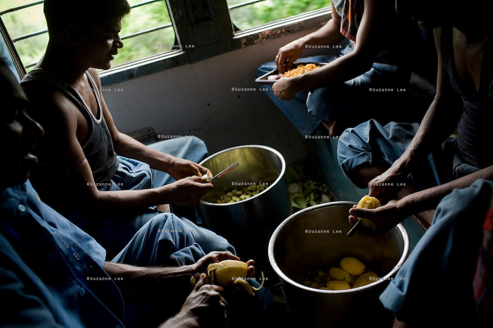 Kithcen helpers peel vegetables in the pantry car on the Himsagar Express 6318 on 8th July 2009.. .6318 / Himsagar Express, India's longest single train journey, spanning 3720 kms, going from the mountains (Hima) to the seas (Sagar), from Jammu and Kashmir state of the Indian Himalayas to Kanyakumari, which is the southern most tip of India...Photo by Suzanne Lee / for The National