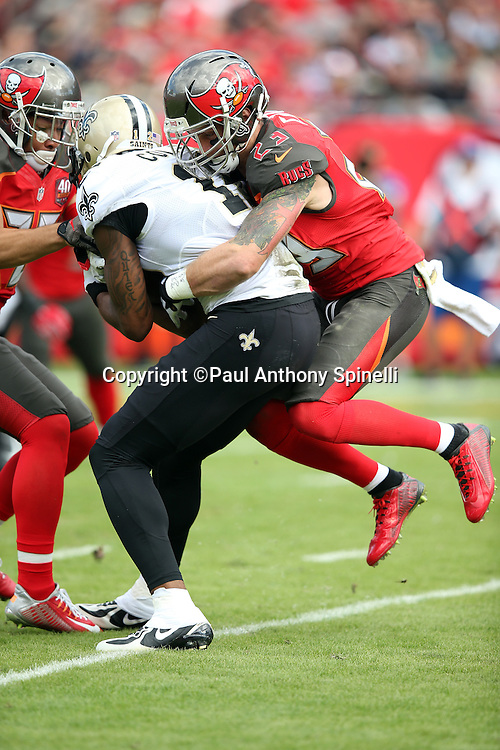 Tampa Bay Buccaneers strong safety Chris Conte (23) gets a ride on the back of New Orleans Saints wide receiver Marques Colston (12) as he catches a pass for a gain negated by penalty during the 2015 week 14 regular season NFL football game against the Tampa Bay Buccaneers on Sunday, Dec. 13, 2015 in Tampa, Fla. The Saints won the game 24-17. (©Paul Anthony Spinelli)