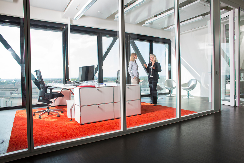 Two women talking in a modern office space