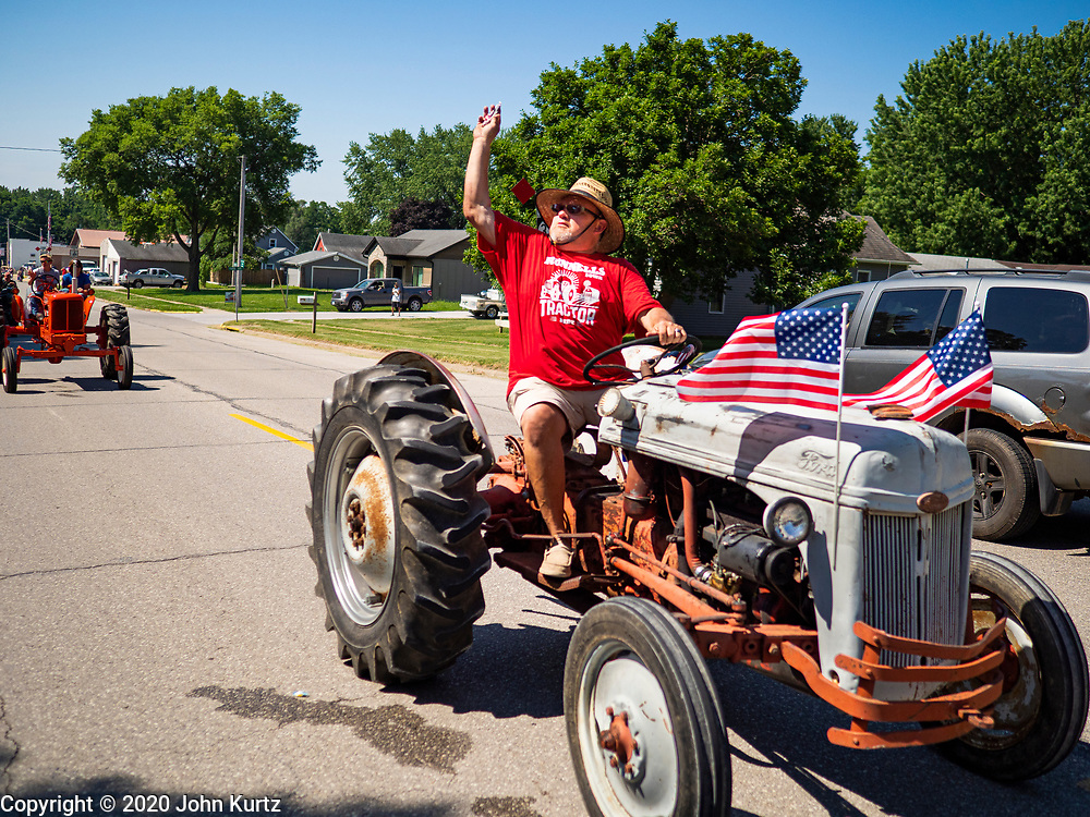 04 JULY 2020 - RUNNELLS, IOWA: A man on a tractor throws candy during the 4th of July tractor parade in Runnells, a small community about 25 miles from Des Moines. Most of the Independence Day parades in central Iowa were cancelled because of the COVID-19 (Coronavirus) pandemic. People in Runnells made the decision to go ahead with their parade, the first 4th of July parade in the town in recent memory. Most of the people in the parade were farmers, who drove their tractors through the town.     PHOTO BY JACK KURTZ