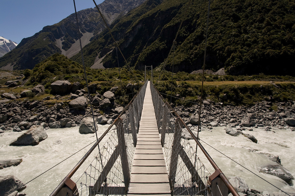New Zealand, South Island, Aoraki Mount Cook National Park, Wooden swinging bridge crosses river on Hooker Valley trail through Southern Alps on clear summer morning