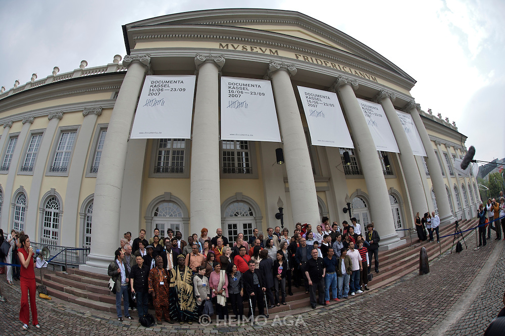 documenta12. Official photo op of documenta artists at Fridericianum. With  Artistic Director Roger M. Buergel (m., red t-shirt and suit) and Curator Ruth Noack.
