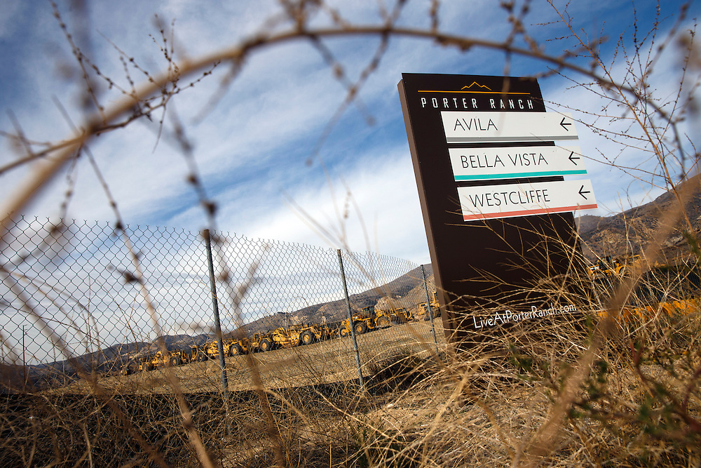 Signage directs prospective buyers to new housing developments under construction in the Porter Ranch neighborhood as methane gas leaks from the SoCalGas Aliso Canyon Storage Facility well SS-25 in the Porter Ranch neighborhood of Los Angeles, California on Sunday, January 3, 2016. The Aliso Canyon gas leak (also called Porter Ranch gas leak) was a massive natural gas leak that started on October 23, 2015. According to Wikipedia, an estimated 1,000,000 barrels per day was released from a well within the underground storage facility in the Santa Susana Mountains near Porter Ranch. The second-largest gas storage facility it belongs to the Southern California Gas Company (SoCalGas), a subsidiary of Sempra Energy. On Jan. 6, 2016, Governor Jerry Brown issued a State of Emergency. The Aliso gas leak carbon footprint is said to be larger than the Deepwater Horizon leak in the Gulf of Mexico. On Feb. 11, 2016 the gas company reported that it had the leak under control. On Feb. 18 state officials announced that the leak was permanently plugged. An estimated 97,100 tonnes of methane and 7,300 tonnes of ethane was released into the atmosphere, making it the worst natural gas leak in U.S. history in terms of its environmental impact. © 2016 Patrick T. Fallon
