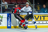 KELOWNA, CANADA - DECEMBER 7:  Braydyn Chizen #22 of the Kelowna Rocketsj is checked by Dino Kambeitz #25 of the Victoria Royals during second period on December 7, 2018 at Prospera Place in Kelowna, British Columbia, Canada.  (Photo by Marissa Baecker/Shoot the Breeze)