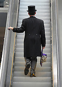 © Licensed to London News Pictures. 21/06/2012. Ascot, UK A man carries a ladies hat up the escalator. Ladies Day at Royal Ascot 21st June 2012. Royal Ascot has established itself as a national institution and the centrepiece of the British social calendar as well as being a stage for the best racehorses in the world.. Photo credit : Stephen Simpson/LNP