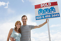 Man embracing woman holding sold sign against sky