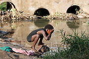Young girl washing her face in the Ngombe settlement's only water source used for washing, laundry and sewage. Lusaka. Zambia. ©WaterAid / Zute  Lightfoot.
