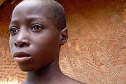 Benin, Boukoumbe April 21, 2005 - Young man with facial scars, in front of a wall with the same signs