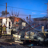 Firefighters with the McKinley County Fire Department work to put out the elates that engulfed a house on the North side of Gallup off Jefferson Avenue near Strong Drive Tuesday.