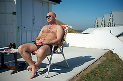 © Licensed to London News Pictures. 28/03/2012..Saltburn, England..As temperatures rise this week the beach at Saltburn in Cleveland attracts the visitors as they enjoy the warm weather. Tom Turner  from Saltburn enjoys the sun as he sits outside his beach hut on Saltburn promenade...Photo credit : Ian Forsyth/LNP