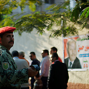Egyptian men queue outside a voting poll at Masr El Gdeeda district in Cairo.