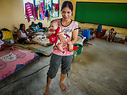 24 JANUARY 2018 - LIGAO, ALBAY, PHILIPPINES: CHRISTINA VILLAS with her infant daughter, JENEVIE BORJAL, 3 months old, in an evacuation center in a school in Ligao. They were evacuated from their home Tuesday, 23 January. The Mayon volcano continued to erupt Tuesday night and Wednesday forcing the Albay provincial government to order more evacuations. By Wednesday evening (Philippine time) more than 60,000 people had been evacuated from communities around the volcano to shelters outside of the 8 kilometer danger zone. Additionally, ash falls continued to disrupt life beyond the danger zones. Several airports in the region, including the airport in Legazpi, the busiest airport in the region, are closed indefinitely because of the amount of ash the volcano has thrown into the air.    PHOTO BY JACK KURTZ