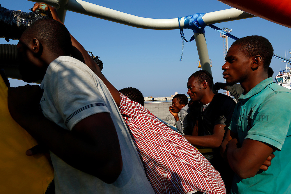 Migrants look out from the deck of the Medecins san Frontiere (MSF) rescue ship Bourbon Argos before disembarking in Trapani, on the island of Sicily, Italy, August 9, 2015.  Some 241 mostly West African migrants on the ship arrived on the Italian island of Sicily on Sunday morning, according to MSF.<br /> REUTERS/Darrin Zammit Lupi <br /> MALTA OUT. NO COMMERCIAL OR EDITORIAL SALES IN MALTA