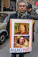 "Rome, Italy. 16th January 2016<br /> Protester holding a sign with a picture of Colonel Muammar Gaddafi with the words: ""murdered"", during Anti-war demonstration on the 25th anniversary of the bombings in Iraq and against military spending, organized by the union USB, and the social platform Eurostop."