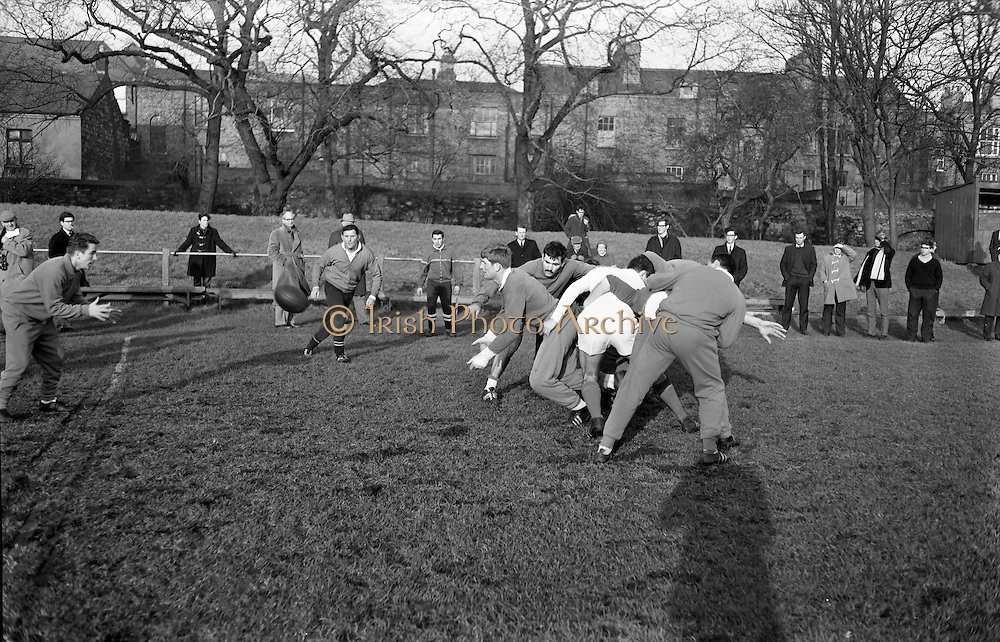 W Spanghero, gets the ball away from a scrum as A Gruarin, prop forward, closes in, .Jean Prat, coach, watches from the left, ..Irish Rugby Football Union, Ireland v France, Five Nations, French team practice at College Park, Dublin, Ireland, Friday 22rd January, 1965,.22.1.1965, 1.22.1965,..Referee- D G Walters, Welsh Rugby Union, ..Score- Ireland 3 - 3 France, ..French Team, ..P Dedieu, Wearing number 15 French jersey, Full Back, A S Biterroise Rugby Football Club, France,. .J Gachassin, Wearing number 11 French jersey, Left Wing, F.C Lourdais Rugby Football Club, France, ..G Boniface, Wearing number 12 French jersey, Left Centre, Stade Montois Rugby Football Club, France,..J Pique, Wearing number 13 French jersey, Right Centre, S Paloise Rugby Football Club, France,..C Darrouy, Wearing number 14 French jersey, Right Wing, Stade Montois Rugby Football Club, France,..J Capdouze, Wearing number 10 French jersey, Stand Off, S Paloise Rugby Football Club, France,..L Camberabero, Wearing number 9 French jersey, Scrum Half, La Voulte Sportif Rugby Football Club, France,..J Berejnoi, Wearing number 1 French jersey, Forward, S C Tulliste Rugby Football Club, France,..J Cabanier, Wearing number 2 French jersey, Forward, U S Montalbanaise Rugby Football Club, France,..A Gruarin, Wearing number 3 French jersey, Forward, R.C Toulonnais Rugby Football Club, France,..W Spanghero, Wearing number 4 French jersey, Forward, R.C Narbonnais Rugby Football Club, France,..D Dauga, Wearing number 5 French jersey, Forward, Stade Montois Rugby Football Club, France,..M Lira, Wearing number 6 French jersey, Forward, La Voulte Sportif Rugby Football Club, France,..A Herrero, Wearing number 8 French jersey, Forward, R.C Toulonnais Rugby Football Club, France,..M Crauste, Wearing number 7 French jersey, Captain of the French team, Forward, F.C Lourdais Rugby Football Club, France, .