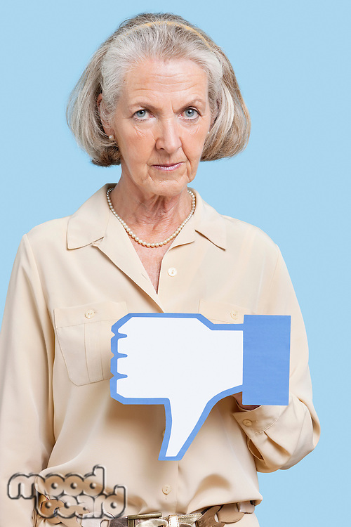 Portrait of senior woman with fake dislike button against blue background