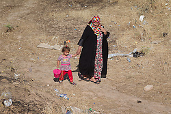 © Licensed to London News Pictures. 25/06/2014. Khanaqin, Iraq. Maya (3) and her mother Rafida Ha'di (23), both Iraqi refugees from the front line town of Jalawla walk through wasteland next to a refugee camp on the outskirts of Bahari Taza village in Iraq. Located on the outskirts of Khanaqin, a town just 20 minutes from the front-line of the battle with ISIS insurgents, the Bahari Taza refugee camp, and its satellite camps, now house around 600 families from southern Iraq. Built by the local village leader to meet the influx of refugees from nearby Jalawla and Saidia, where intense fighting is still taking place. Turkman, Arab and Kurd, both Sunni and Shia, all live together in tents, barns and unfinished buildings waiting for the conflict to end. Photo credit: Matt Cetti-Roberts/LNP