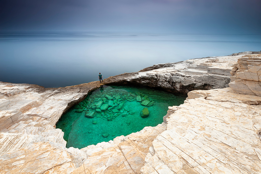 Green lake in the rock shore by the sea