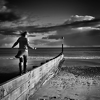 Young girl alone on beach walking along wooden breaker in England under a cloudy sky