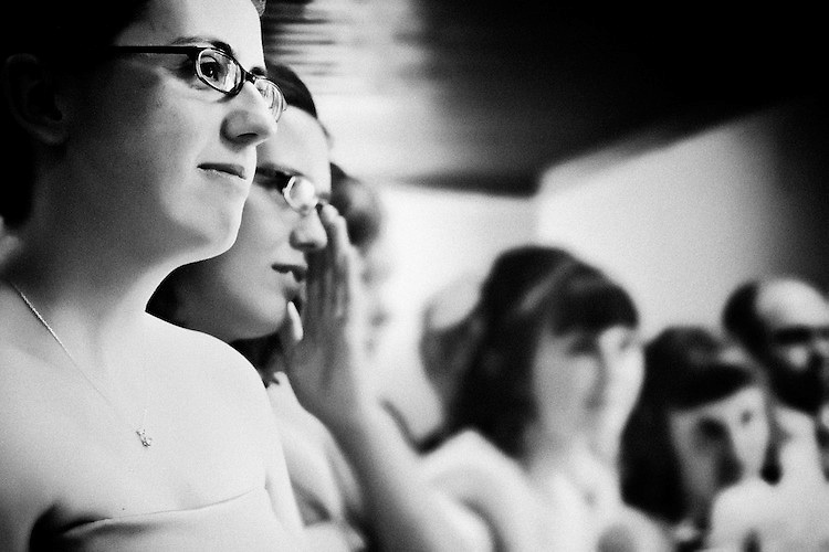 Katie's sisters listen to the sermon at her wedding ceremony. <br /> <br /> To view Katie and Brad's complete Wedding Gallery Collection, visit the Client Area and log-in. You'll be able to view all images as a slideshow, order prints and more.<br /> <br /> &copy; Images of a Promise by Dean Oros Photo + Design