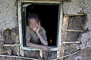 "Victor Owino, 9, stares at the window of his home he shares with his four older brothers in Homa Bay, Kenya. Victor was crawling when he lost his mother to complications from AIDS a year after his father passed away from the same disease.  His aunt raised him for the first years of his life but he chose to return to live with his brothers once he was older. The oldest brother Abraham, 16, was 7 when his mother died. He has been the head of the family ever since. He dropped out of school to support his four younger brothers and earns a living by giving people rides on a rented ""bora-bora"" (moped).  The district of Nyanza in Kenya has a very high incidence of HIV and many children have been orphaned as a result. The Owino brothers  children receive support from The Child Behind Project, which assists Orphans and Vulnerable Children (OVC) in the area. They receive help with school fees, uniforms, medical care, blankets, grains, and thrice monthly visits from a community health worker"