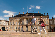 A old couple walking in front of Copenhagen's Amalienborg Palace set against a summer sky.