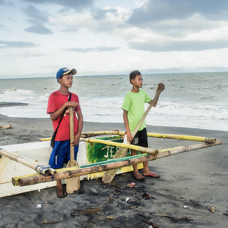 L-R: Jerald (15) and Arbin (15) build a small boat from scraps that they found on the beach in Tanawan.