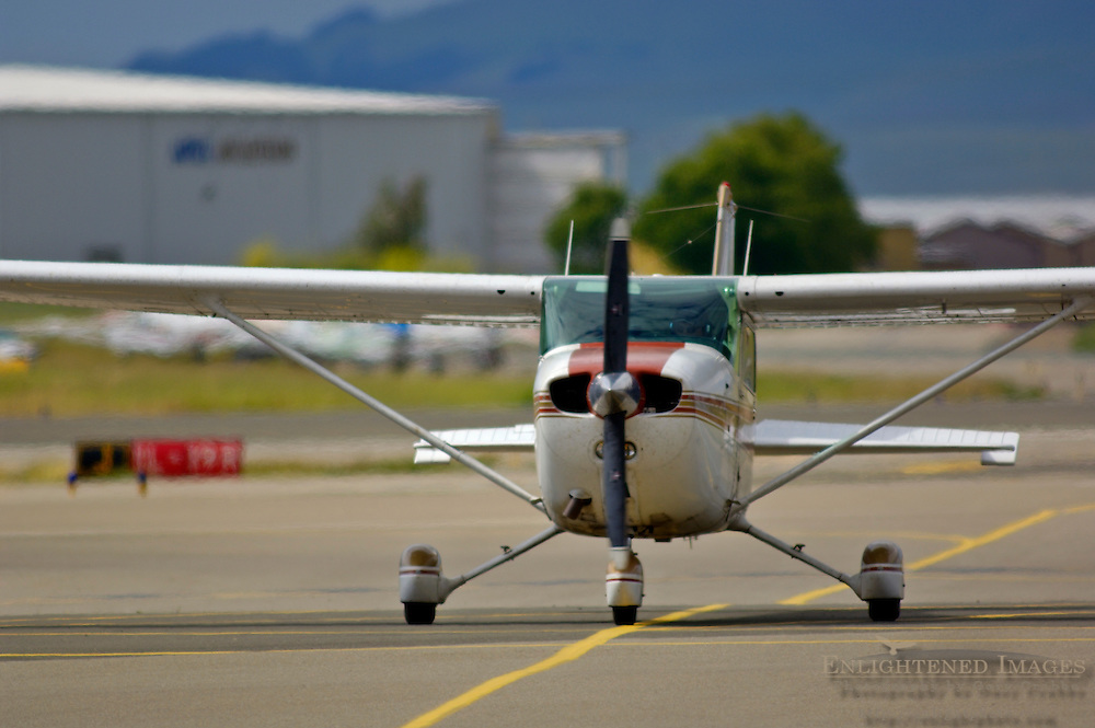 Small Cessna single engine airplane taxiing on taxiway at Buchanan Field airport, California