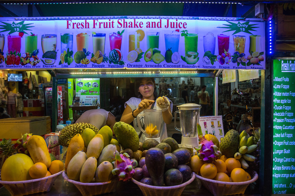 A Cambodian woman slices mango into a blender with knife on her fresh fruit shake and juice market stall on Street 10 in Siem Reap, Cambodia, Asia.  (photo by Andrew Aitchison / In pictures via Getty Images)