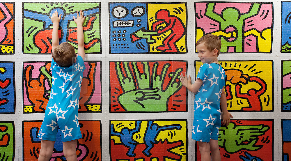 © Licensed to London News Pictures. 27/06/2013. London, UK. Twins Jonah and Beau (6) are seen with a 32,256 piece Keith Haring jigsaw puzzle (Hamleys price GB£200) at the Christmas in June press event at Hamleys toy shop in London today (27/06/2013).  Held in retailers world famous Regents Street store, the event showcases the predicted top toys for Christmas 2013. Photo credit: Matt Cetti-Roberts/LNP