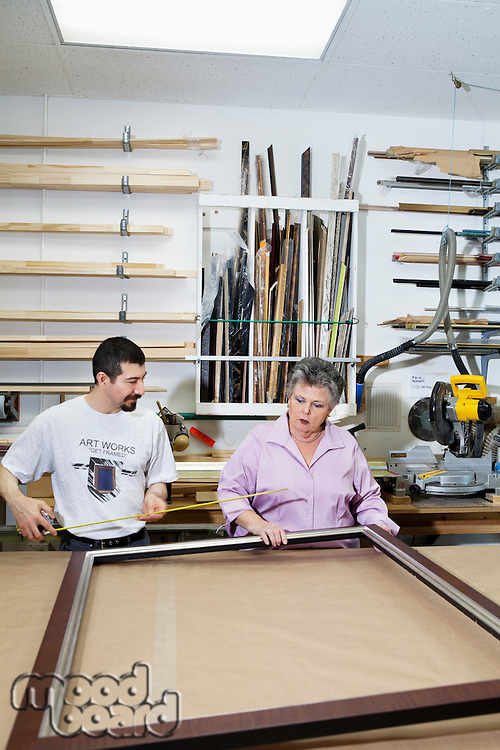 Mature employee measuring picture frame with senior owner in workshop