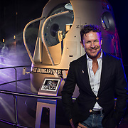 Felix Baumgartner poses for a portrait in front of the Stratos capsule that is on display at the Magna Science Adventure Centre in Rotherham, UK on July 23, 2015