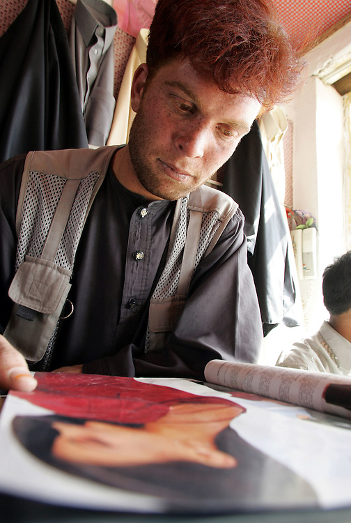 21 October 2004&amp;#xD;&amp;#xA;Kabul, Afghanistan.&amp;#xD;&amp;#xA;Ex Mujahedeen turn to peacetime profesions.&amp;#xD;&amp;#xA;&amp;#xD;&amp;#xA;Sardar Mohamed an illiterate former mujahedeen fighter flicks through a womens fashion magazine in a tailors shop in Kabul, Afghanistan. &amp;#xD;&amp;#xA;&amp;#xD;&amp;#xA;Sardar is one of more than 21,000 former fighters who have been reintergrated into peacetime society thanks to a UN run disarmament program.<br />