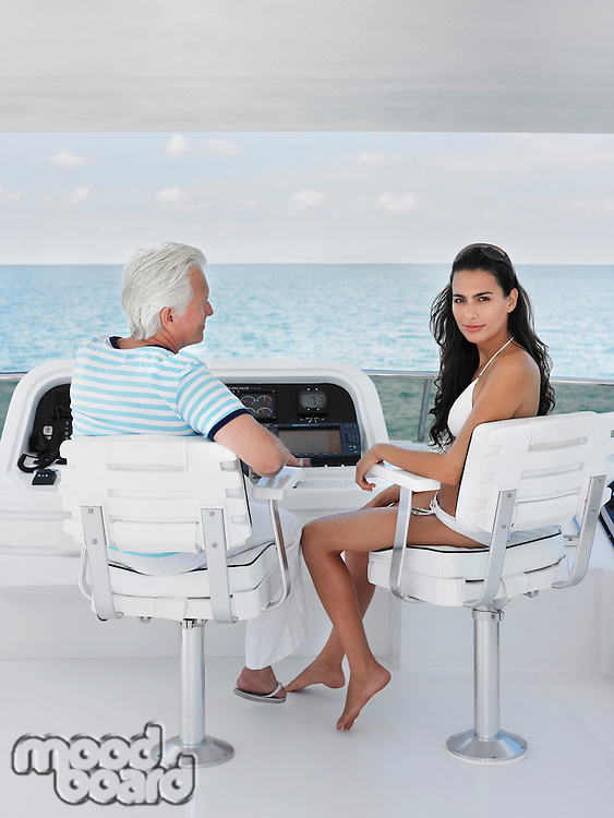 Middle-aged man and young woman sitting at helm of yacht