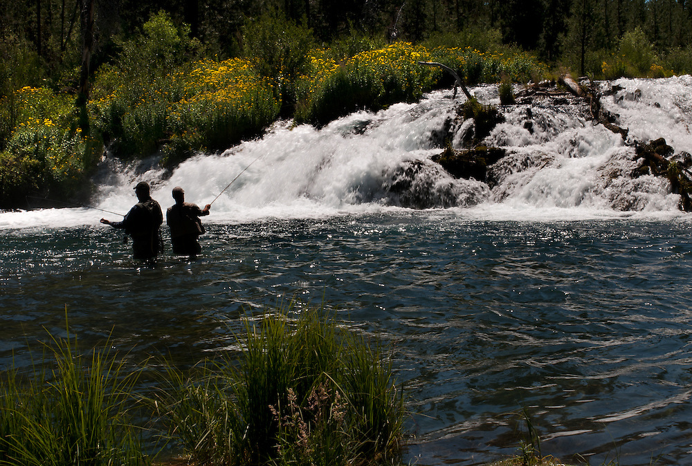 A pair of fisherman try their luck for trout below a waterfall.