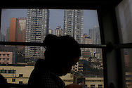 A young woman commutes across the city of Chongqing in a cable car in  China, Sunday, Nov. 2, 2008. Block after city block, towers of concrete, steel and glass fill the skyline. .Teeming and congested, the intensely urban landscapes of China's biggest cities show a glimpse of what the future will hold for the rest of the country.In the sprawling megacities of Beijing, Shanghai and Chongqing, where populations exceed 10 million people, extreme urban density means that the number of people living within a few square blocks here is equal to the population of entire mid-size U.S. cities. .China's urban population soared to 607 million people last year _ nearly equaling the 700 million living in the countryside. The country's headlong plunge toward urbanization continues unabated as tens of millions of migrants from the countryside flood to cities in search of money, jobs and other opportunities