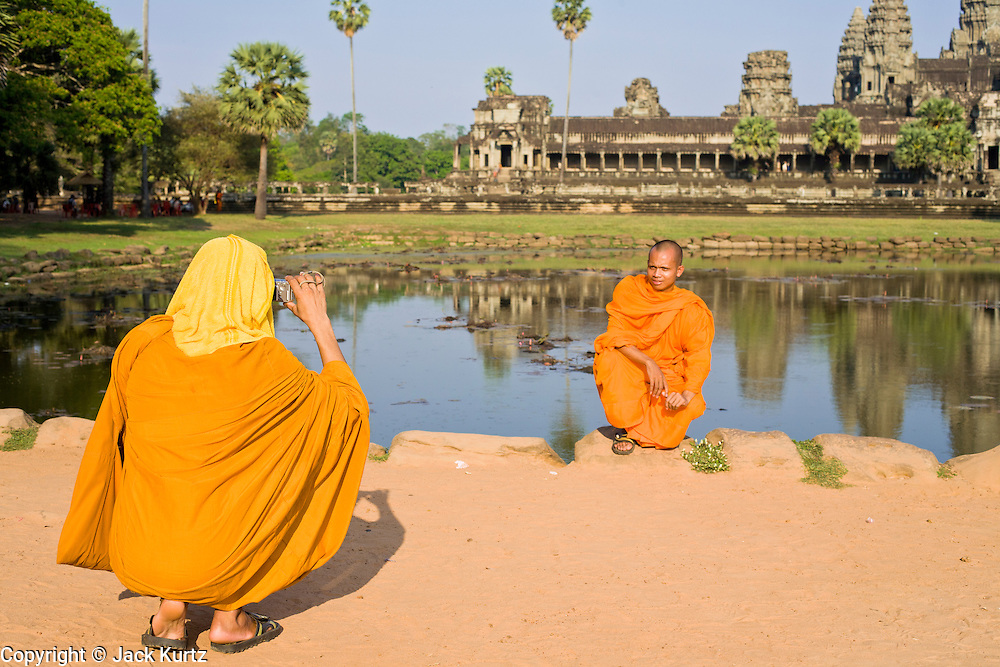 19 MARCH 2006 - SIEM REAP, SIEM REAP, CAMBODIA: Buddhist monks pose for photos in front of the Angkor Wat complex near Siem Reap, Cambodia. More than one million tourists are expected to visit Angkor in 2006 and it is the largest tourist attraction in Cambodia. It is also still one of the most important centers of Buddhism in Cambodia. PHOTO BY JACK KURTZ